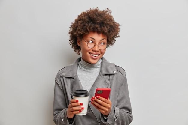 긍정적으로 잘 생긴 학생은 커피를 마시고, 휴대 전화와 일회용 컵을 손에 들고, 기뻐하며 외모에 세련된 회색 재킷을 입었습니다.