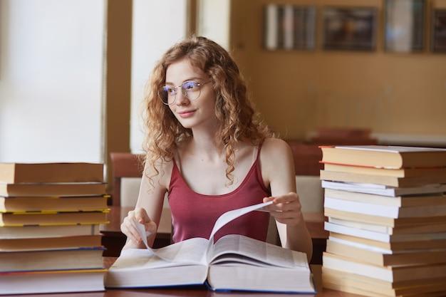 Позитивная красивая молодая девушка с приятным выражением лица, в красном топе и стильными очками, трогательная огромная книга, готовящая свой студенческий проект в классе.