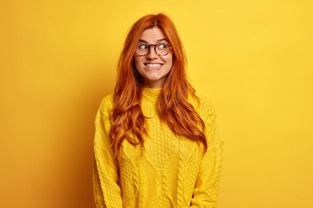 ポジティブな格好良い若い女性は、カジュアルなジャンパーに身を包んだ素敵なオファーを熟考する唇をかむことはさておき、幸せな神秘的な表情で自然な生姜髪のルックスを持っています。