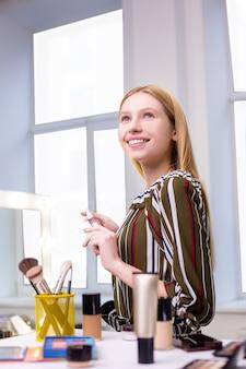 彼女の美しさを楽しみながら笑顔のポジティブな格好良い若い女性