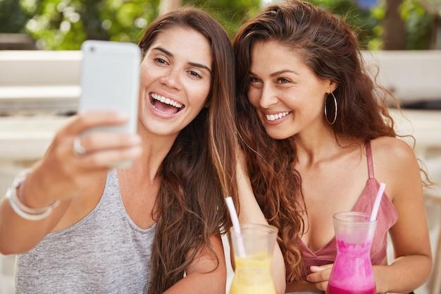 気分が良い前向きなゴージャスな女性は、居心地の良い屋外のカフェテリアでレクリエーションの時間を楽しみ、自撮りのポーズをとり、新鮮なスムージーを飲み、一緒に楽しみます。