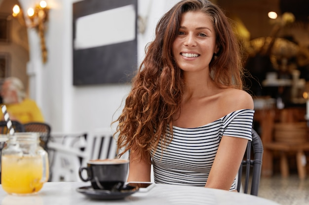 Positive gorgeous young female feels happy in coffee shop