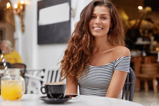 Позитивная великолепная молодая женщина чувствует себя счастливой в кафе