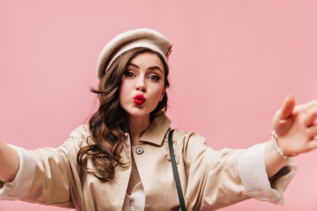 Positive green-eyed girl dressed in beige trench coat takes selfie on pink background.