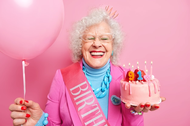 Positive grey haired grandma celebrates birthday poses with cake and inflated balloon cares about herself looks beautiful in her old age smiles broadly has white teeth has festive mood during party
