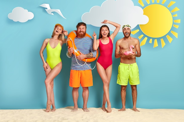 해변에서 포즈를 취하는 친구의 긍정적 인 그룹
