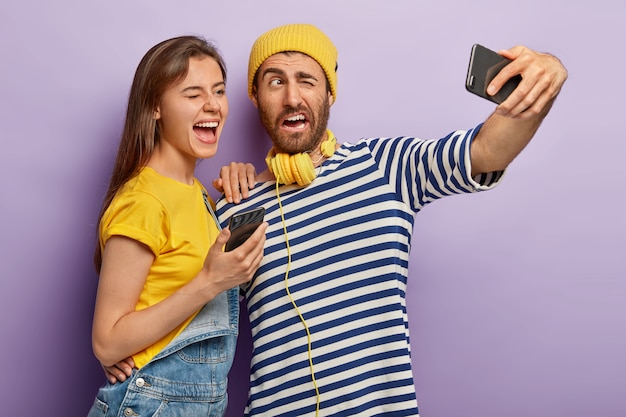 Positive guy and female blink eyes, pose in front of cell phone camera, make photo for internet blog, take selfie, have glad expressions