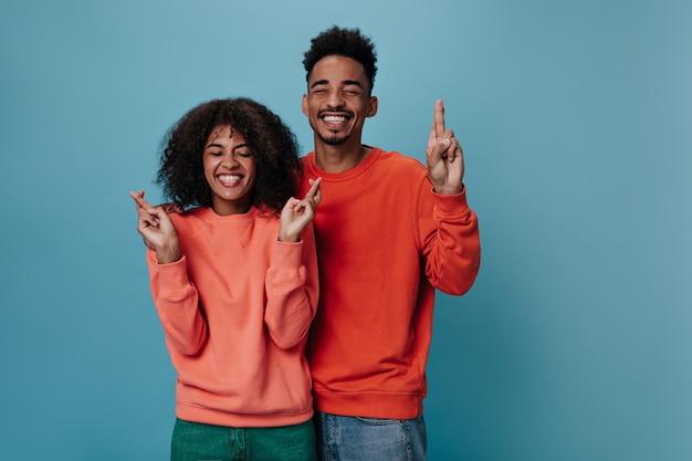 Positive guy and girl in orange sweatshirts crosses fingers on blue wall