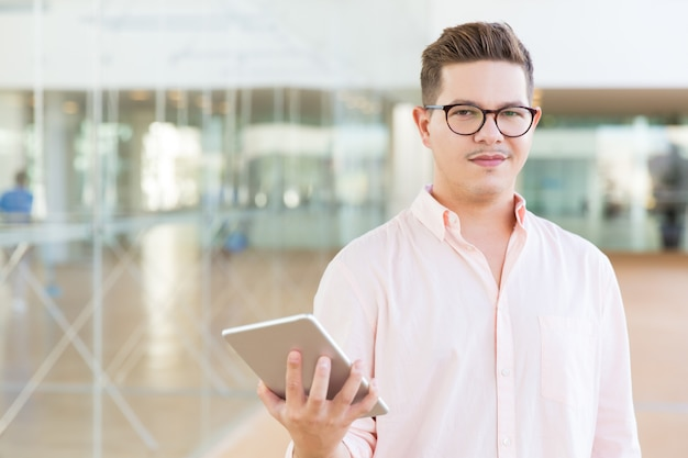 Positive guy in glasses holding tablet, looking