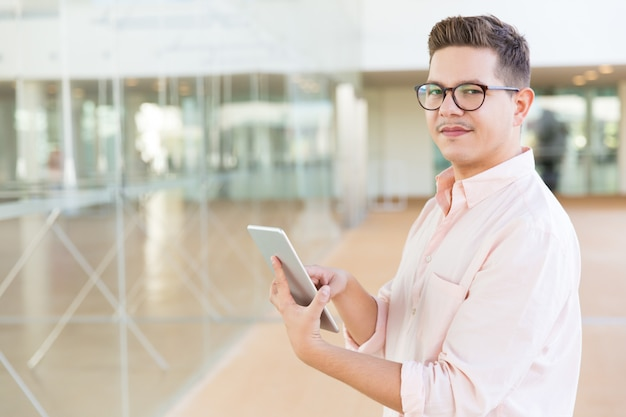 Positive guy in glasses holding tablet in office or hotel hall