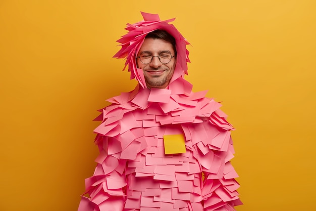 Positive guy has pink adhesive notes stuck around body and head, makes creative paper costume from stickers, wears spectacles, works in office, isolated over yellow wall, keeps eyes shut