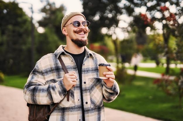 모자와 선글라스를 쓴 긍정적인 남자는 배낭을 메고 도시를 걷는 동안 커피를 들고 있다