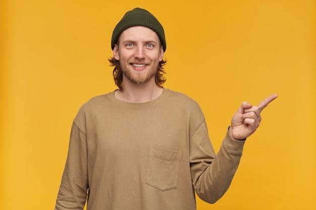 Позитивный парень со светлыми волосами, бородой и усами. в зеленой шапке и бежевом свитере. и указывая пальцем вправо на пространство для копирования, изолированное над желтой стеной
