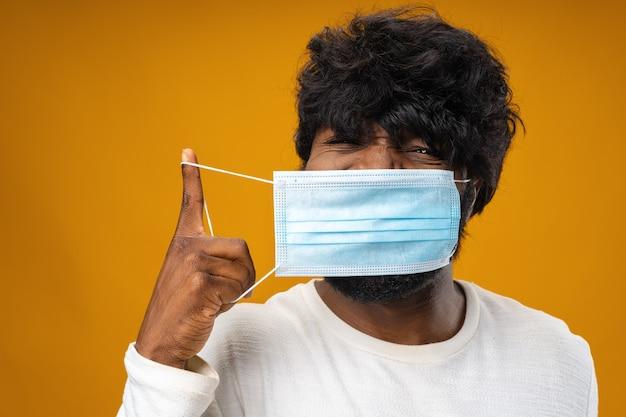 Позитивный красивый афро-американский мужчина с медицинской маской на желтом фоне
