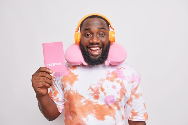 Positive handsome afro american man holds passport listens music via headphones wears neck pillow for comfortable travel dressed in washed out t shirt isolated over white wall