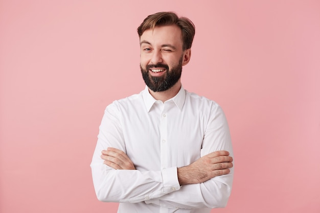 Positivo bel ragazzo barbuto con capelli castani corti che strizza l'occhio felicemente davanti mentre posa sul muro rosa, incrociando le mani sul petto, vestito con una camicia bianca