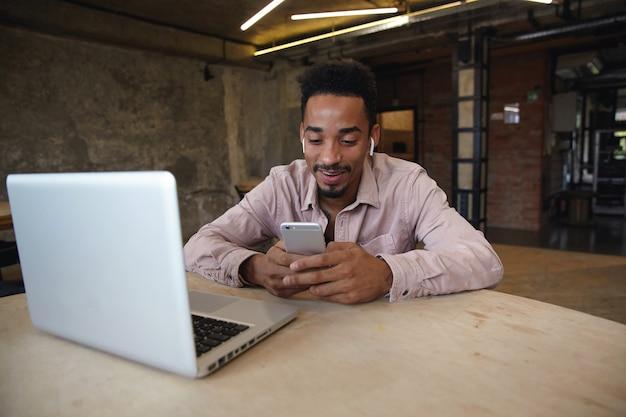 Uomo barbuto bello positivo con pelle scura che indossa una camicia beige, lavora a distanza dallo spazio di coworking, tiene il cellulare in mano e controlla i social network