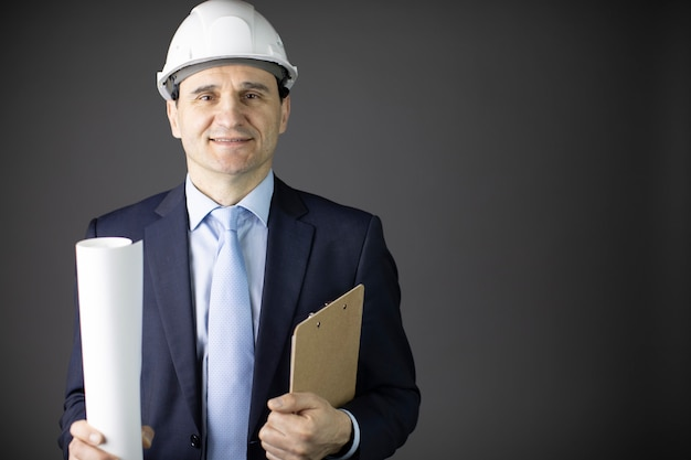Positive handsome constructor in helmet formal clothing holds drawing smiling