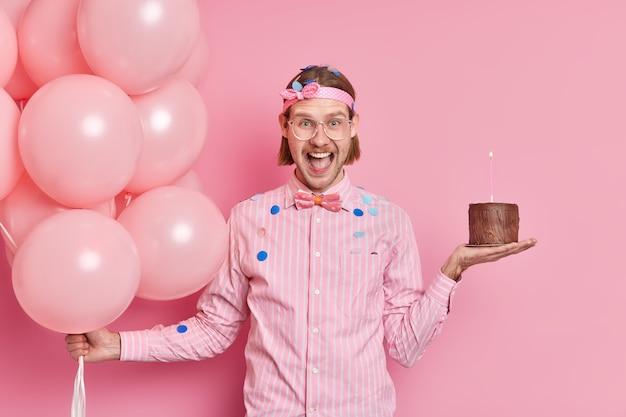 긍정적 인 잘 생긴 유럽 남자는 나비 넥타이와 셔츠를 입고 작은 초콜릿 케이크를 보유하고 부풀어 오른 풍선 무리가 분홍색 벽 위에 고립 된 생일 파티를 즐깁니다.