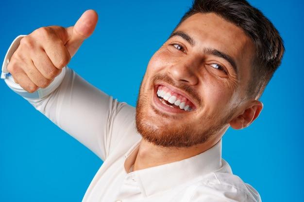 Позитивный красивый латиноамериканский бизнесмен, показывая большой палец вверх жест