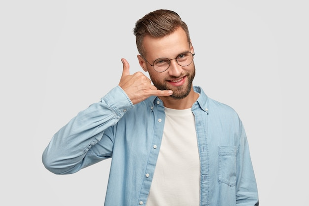 Positive handsome male makes phone gesture, pretends speaking over smart phone, has cheerful expression, dressed in fashionable shirt, isolated over white wall. people and communication concept