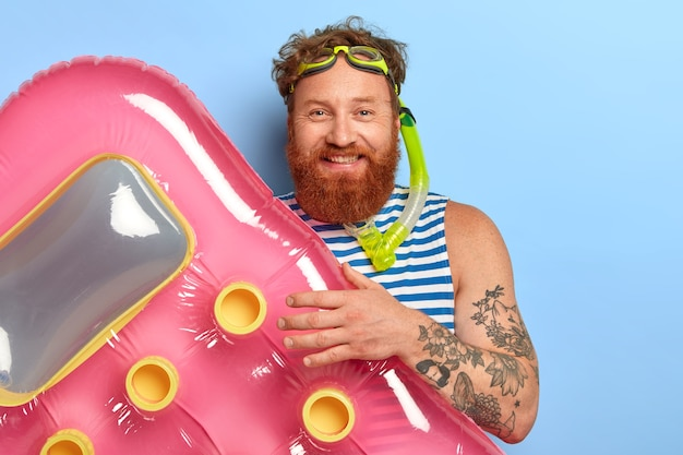 Positive handsome male traveler spends summer holidays actively, swims with inflated mattress, wears snorkeling mask, has red curly hair and beard, smiles happily