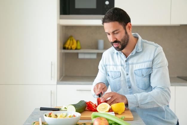 긍정적 인 잘 생긴 남자 요리 샐러드, 부엌에서 자르고 보드에 신선한 야채를 절단. 중간 샷, 복사 공간. 건강 식품 개념