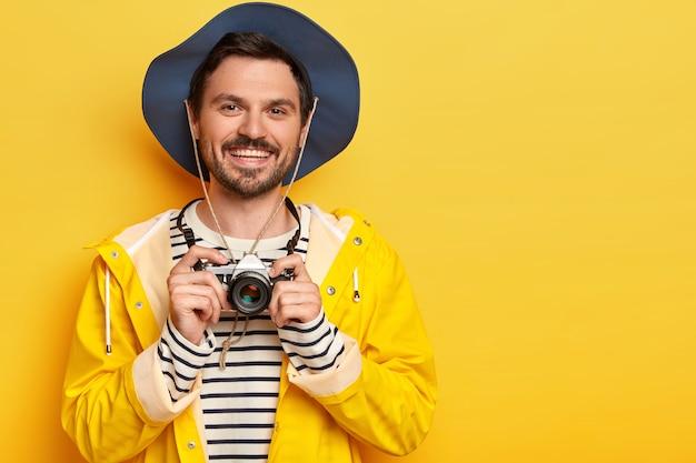 ポジティブなハンサムな男はレトロなカメラを持って、心地よく微笑んで、アクティブな服を着て、黄色の背景に対してポーズをとります。