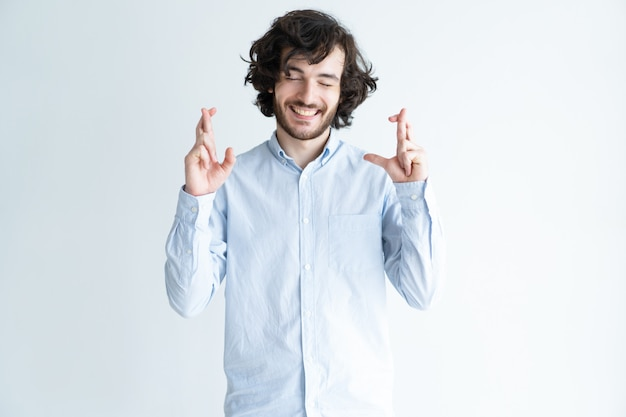 Positive handsome man showing crossed fingers gesture