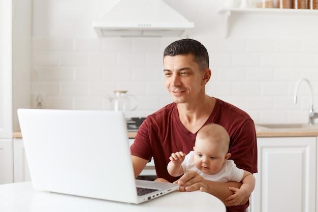 バーガンディのカジュアルなtシャツを着て、ノートブック画面を見て、ベビーシッターをしながらノートパソコンで作業し、白いキッチンでポーズをとって、黒髪のポジティブなハンサムな男。