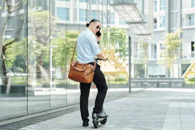 電動スクーターに乗って電話でサングラスをかけたポジティブでハンサムでスタイリッシュな若い男