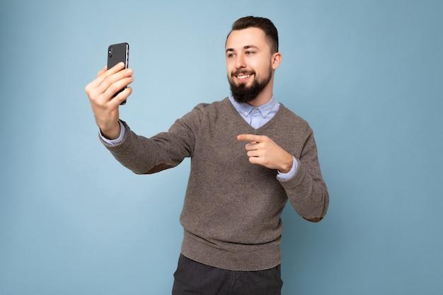 カジュアルな灰色のセーターを着てひげを持つポジティブなハンサムな若いブルネットの無精ひげを生やした男と