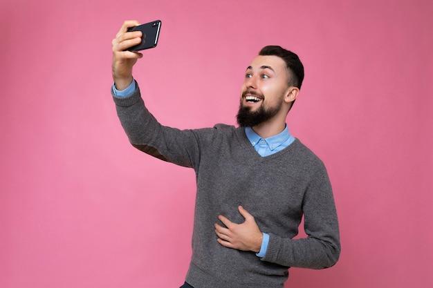 カジュアルなグレーのセーターを着てひげを生やした肯定的なハンサムな若いブルネットの無精ひげを生やした男