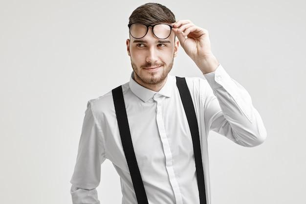 Позитивный красивый молодой кавказский мужчина с щетиной и стильной стрижкой смотрит в сторону с уверенной кокетливой улыбкой, одетый в белую элегантную рубашку с подтяжками, держа в руках модные очки