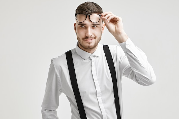 Positive handsome young caucasian man with stubble and stylish haircut looking away with confident flirtatious smile, dressed in white elegant shirt with suspenders, holding his trendy eyeglasses