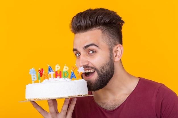 黄色の背景にポーズをとってお誕生日おめでとうの碑文とお祝いのケーキを保持しているブルゴーニュのtシャツの前向きなハンサムな若いヒップスターの男。おめでとうと記念日の概念。