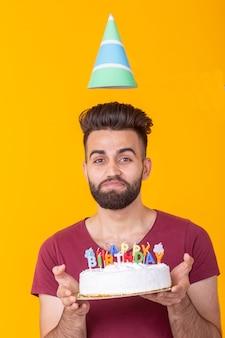 Позитивный красивый молодой битник человек в бордовой футболке держит поздравительный торт с надписью с днем рождения, позирует на желтом фоне. концепция поздравлений и юбилеев.