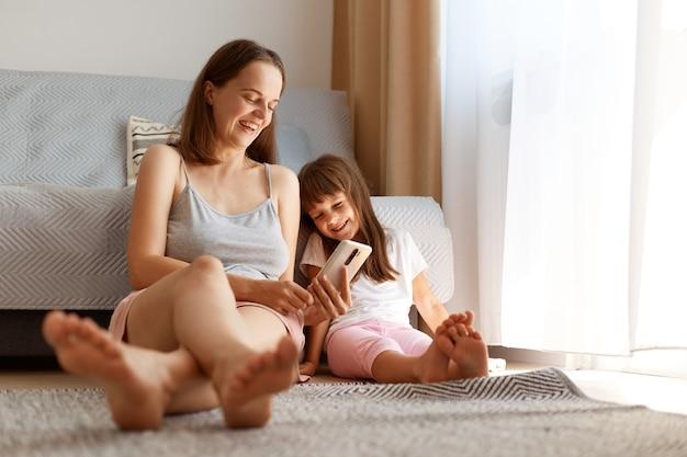 스마트폰을 손에 들고 딸과 함께 바닥에 앉아 웃고, 낙관적인 감정을 표현하고, 아이와 함께 휴대폰을 사용하는 긍정적이고 매력적인 젊은 성인 여성.