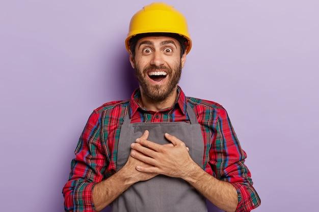 Builder felice positivo, lavora in una società di costruzioni, tiene le mani sul petto, indossa elmetto protettivo giallo, abbigliamento da lavoro, sorride ampiamente