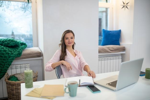 仕事中に彼女のオフィスに座っているポジティブな幸せな実業家