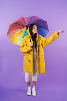 Positive happy cute brunette woman in yellow raincoat posing isolated over purple wall wall holding umbrella.