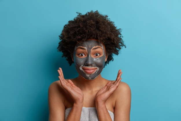 Positive happy dark skinned afro american woman applies facial clay mask, gets beauty treatments, cares abot skin, spreads palms sideways over face, stands wrapped in towel, models indoor. hygiene