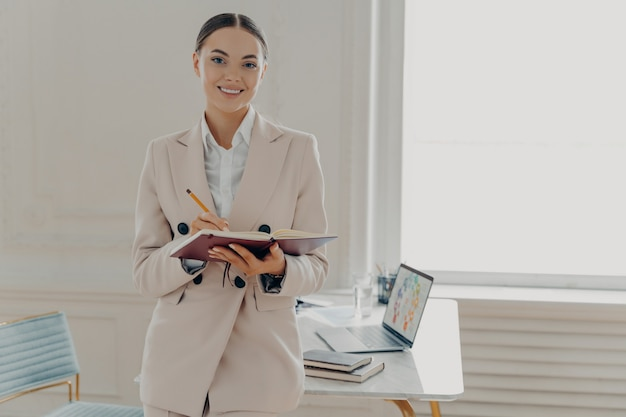 Позитивная счастливая женщина-директор в элегантной одежде, планирующая рабочий день, находясь в хорошем настроении, стоя в современном светлом интерьере офиса, счастливая бизнес-леди делает заметки, работая удаленно дома