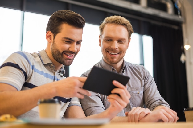 Позитивные счастливые радостные мужчины сидят вместе и смотрят на экран планшета, работая в команде
