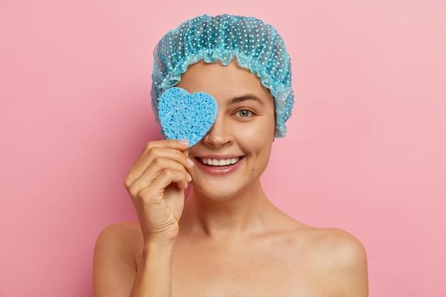 La donna adorabile e felice positiva copre gli occhi con una spugna a forma di cuore, si asciuga il viso per la pulizia, indossa un cappuccio protettivo blu, riceve un trattamento di bellezza, modelli contro il muro rosa. coccole e relax