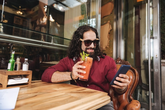 카페에서 휴식을 취하는 동안 그의 음료를 즐기는 긍정적 인 행복한 사람
