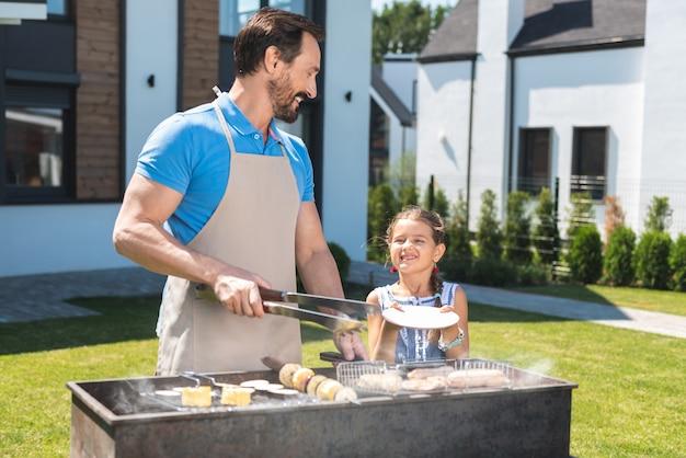 음식을 제공하는 동안 그의 딸을보고 긍정적 인 행복 한 사람