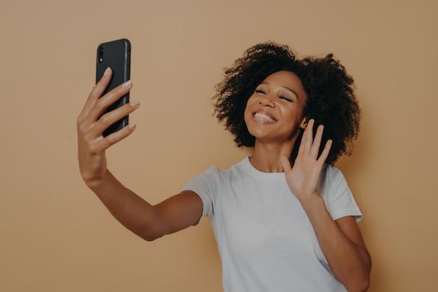 現代のスマートフォンのビデオ通話中にカメラで手を振ってポジティブな幸せな混血の女性