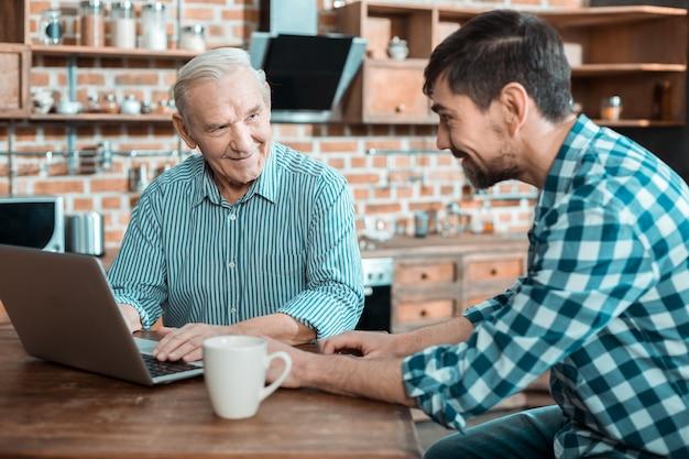 彼にラップトップを使用するように教えている間彼の父に微笑んで話している前向きな幸せないい男
