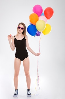 Positive happy smiling cute lovely pretty girl in black swimsuit holding colorful balloons and small macaroons